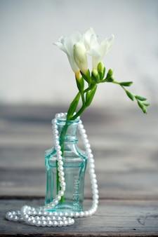Weiße freesienblüten in dekorativen flaschen