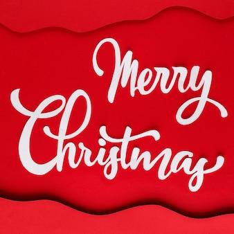 Weiße frohe weihnachtsbeschriftung auf rotem papier mit schichten