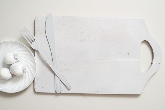 Weiße gabelmesserplatte auf einem alten hölzernen plankenbehälter