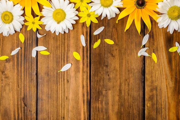 Weiße gänseblümchen und gartenblumen auf einem braunen holztisch