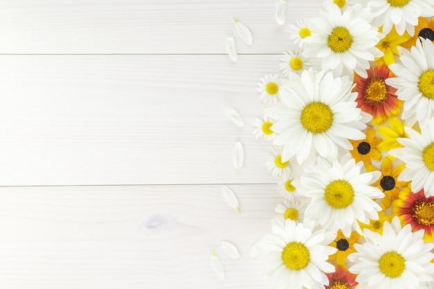 Weiße gänseblümchen und gartenblumen auf einem weißen holztisch.