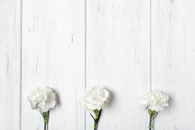 Weiße gartennelken auf holztisch backgeound. platz kopieren