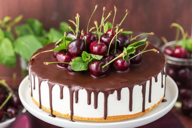 Weiße gelee-torte mit vanille-basis und schokoladenüberzug, dekoriert mit frischen kirschen