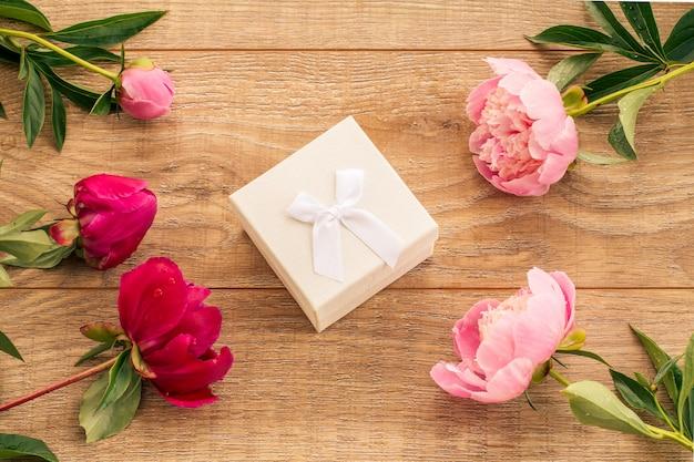 Weiße geschenkbox auf holzbrettern, verziert mit pfingstrosenblüten. ansicht von oben.