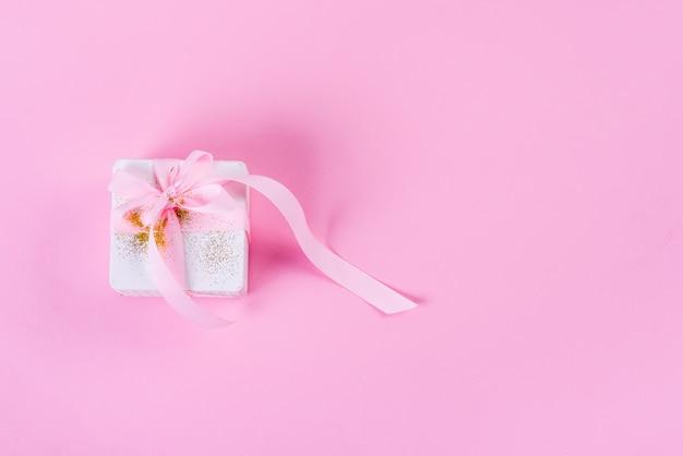 Weiße geschenkbox gebunden mit rosa band auf rosa pastellhintergrund mit kopienraum