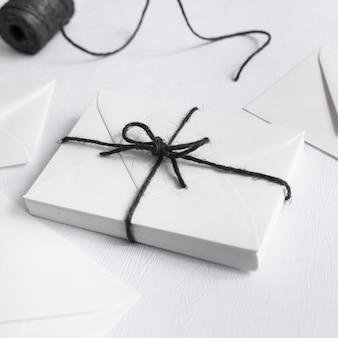 Weiße geschenkbox gebunden mit schwarzer schnur auf weißem hintergrund