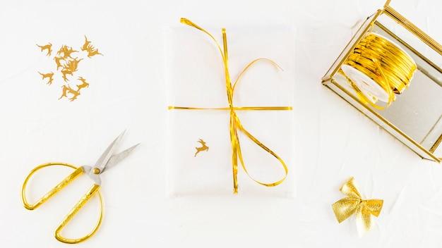 Weiße geschenkbox im kraftpapier nahe scheren und spule des bandes