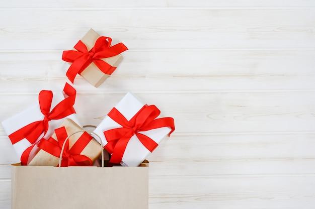 Weiße geschenkbox in roter schleife in einer papiertüte auf weißem holzhintergrund gebunden