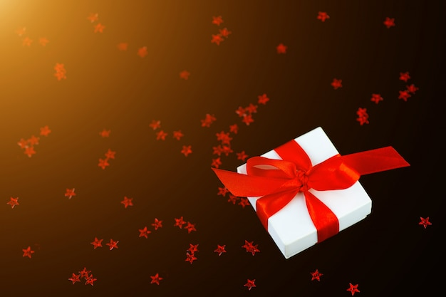Weiße geschenkbox mit einem roten band und einem zerstreuen von sternen auf schwarzem hintergrund.