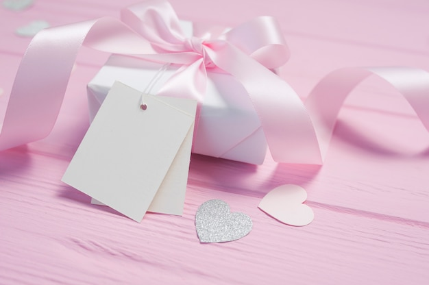 Weiße geschenkbox mit einer rosa satinschleife und einem band auf rosa hölzernem hintergrund. valentinskarte