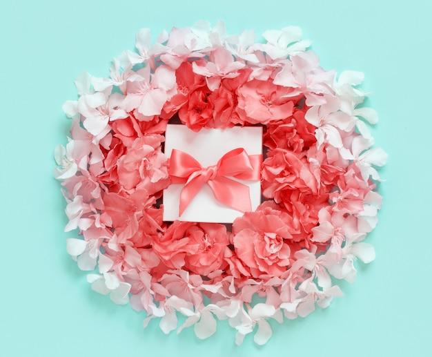 Weiße geschenkbox mit einer schleife zwischen rosa blumen draufsicht auf hellgrünem hintergrund