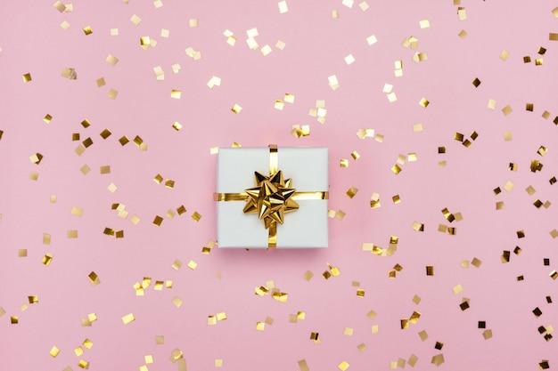Weiße geschenkbox mit goldener schleife auf pastellrosa hintergrund mit glitzer. draufsicht mit freiem speicherplatz.