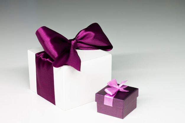 Weiße geschenkbox mit lila band und lila geschenk, auf grauem hintergrund