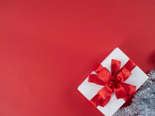 Weiße geschenkbox mit rotem band auf rotem hintergrund