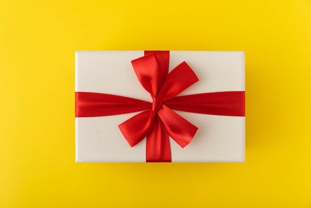 Weiße geschenkbox mit rotem band. präsentation auf gelbem hintergrund