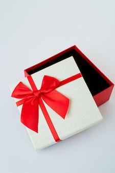 Weiße geschenkbox mit rotem bandbogen auf weiß