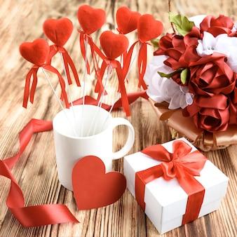 Weiße geschenkbox mit roter riibonschleife, weißer becher mit roten herzen auf stock, herzkarte und rosenblumen vom satinband auf hölzernem hintergrund.