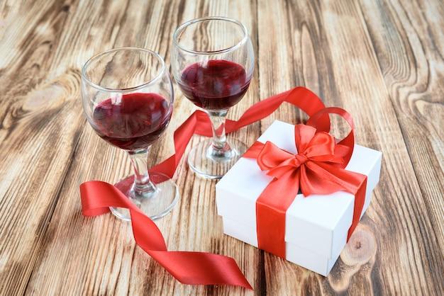 Weiße geschenkbox mit roter satinbandschleife, zwei glas wein und strauß roter und weißer künstlicher rosenblumen auf hölzernem hintergrund.