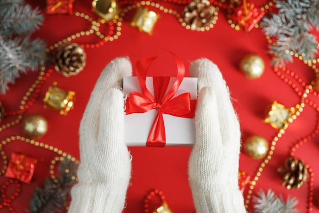 Weiße geschenkbox mit roter schleife in den handschuhen