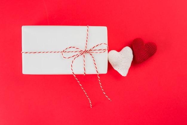 Weiße geschenkbox mit torsion nahe spielzeugherzen