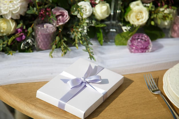 Weiße geschenkbox mit violettem band steht auf einem abendtisch