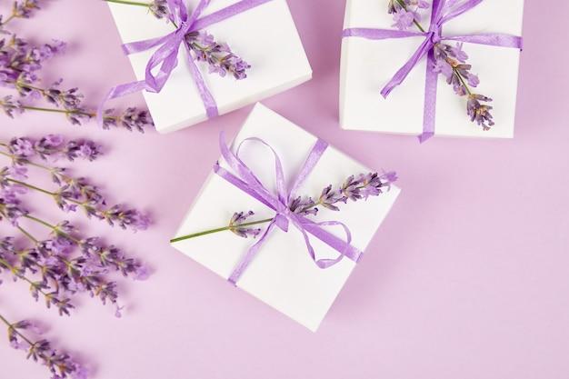Weiße geschenkbox mit violettem band und lavendel