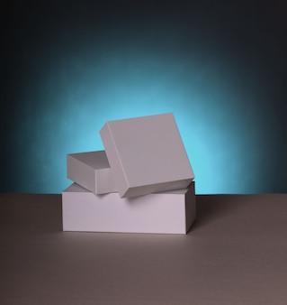 Weiße geschenkboxen. leere geschenkboxen und geschenktüten auf blauem hintergrund mit schatten.