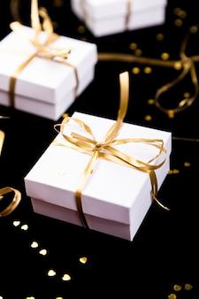 Weiße geschenkboxen mit goldband auf glanzhintergrund. nahansicht.
