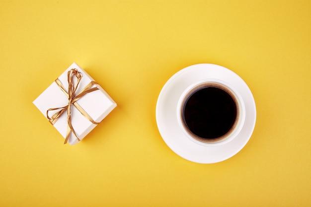 Weiße geschenkboxen mit goldband und schwarzem kaffee