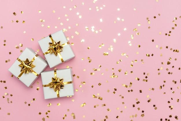 Weiße geschenkboxen mit goldener schleife auf pastellrosa hintergrund mit glitzer. draufsicht mit freiem speicherplatz.