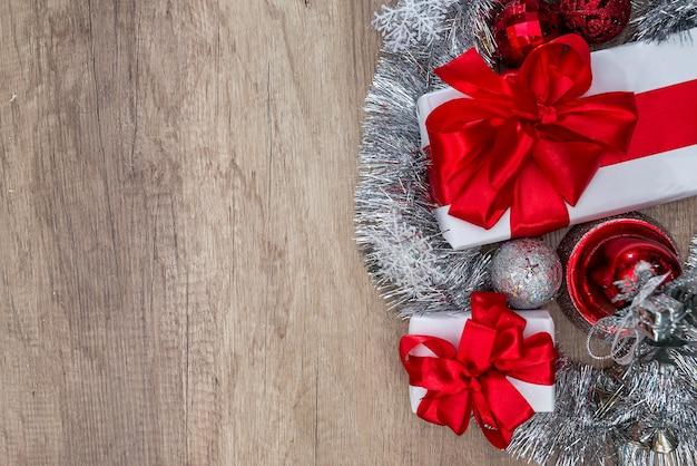 Weiße geschenkboxen mit roten bändern und weihnachtsschmuck