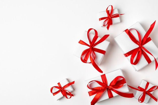 Weiße geschenke mit rotem band auf weißem hintergrund