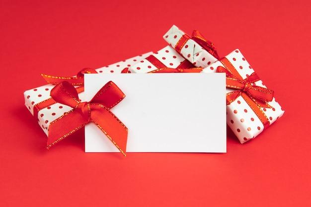 Weiße geschenke verpackt in geschenkpapierbehälter mit festlichem band auf rotem hintergrund mit notizmodell.