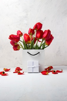 Weiße geschenktüte, kleine weiße geschenkbox und strauß roter tulpen auf einem hellen stein. konzept bietet eine verlobung oder ehe