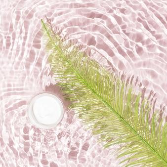 Weiße gesichtscreme und grünes farnblatt im wasser mit kleinen wellen auf weichem pastellrosa hintergrund mit fliesen. luxuriöse weibliche schönheitsprodukte. minimaler stil.