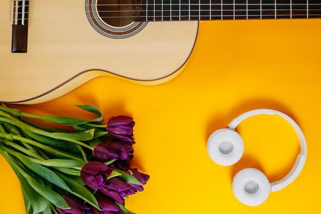 Weiße gitarre und weiße kabellose kopfhörer auf dem orangefarbenen hintergrund, frühlingsblumen, bündel lila tulpen, weiße gitarre und blumen, frühlingsmusikplakat.