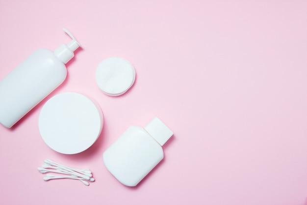 Weiße gläser kosmetik auf rosa