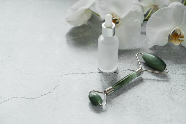 Weiße glas-serumflasche mit guasha-massagerolle für spa und natürliche hautpflege zu hause, körper- und hautpflege, natürliche behandlung, spa-kosmetikprodukt-branding-mockup