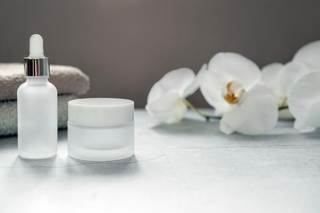 Weiße glasserumflasche und cremedose im badezimmer mit badetüchern und orchideenblüten im hintergrund, natürliche körper- und hautpflege, spa-kosmetikprodukt-branding-mockup