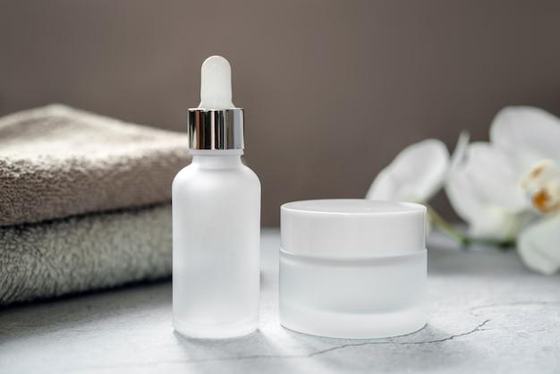 Weiße glasserumflasche und cremedose im badezimmer mit badetüchern und orchideenblüten im hintergrund, natürliche körper- und hautpflege, spa-kosmetikprodukt-branding-modell