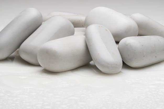 Weiße glatte steine mit wassertropfen auf hellem hintergrund