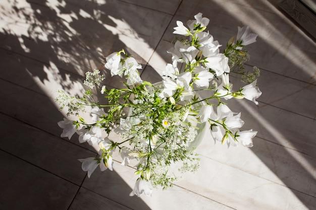 Weiße glockenblumen in einer glasvase. blumen im abendsonnenlicht und im schatten. erstaunliche form, kurve vom weißen gänseblümchenblumentopf mit langem schrägem schatten auf holz für wohnkultur.