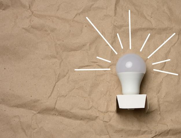Weiße glühbirne mit strahlen auf einem braunen papier, grünes energiekonzept, neue ideen, kopierraum