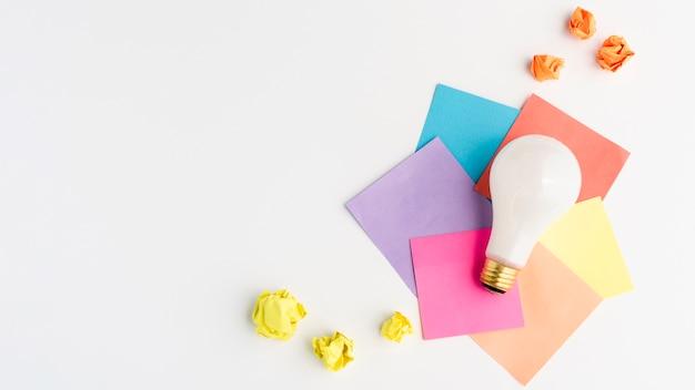 Weiße glühlampe auf bunter klebender anmerkung mit gelb zerknittertem papier
