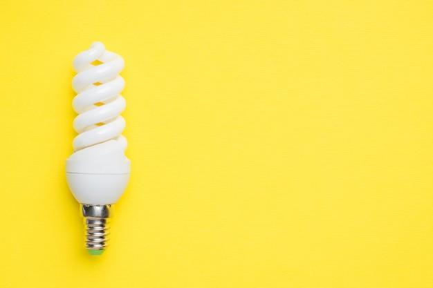 Weiße glühlampe auf hellem gelbem hintergrund mit kopienraum selektiver fokus.