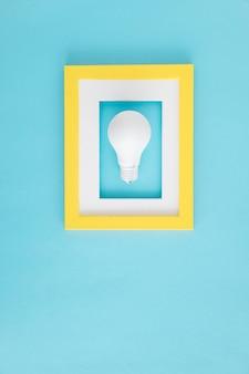 Weiße glühlampe mit gelbem und weißem grenzrahmen über dem blauen hintergrund
