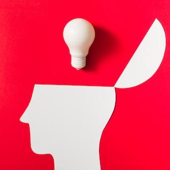 Weiße glühlampe über dem geöffneten papier schnitt kopf gegen roten hintergrund aus