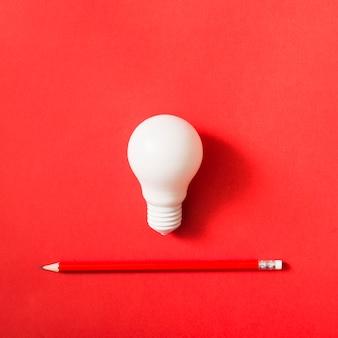 Weiße glühlampe und scharfer roter bleistift auf hellem hintergrund