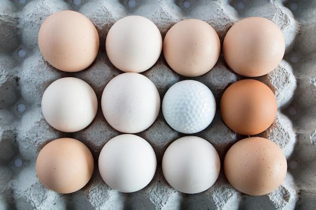 Weiße golfbälle im kasten für eierdekoration