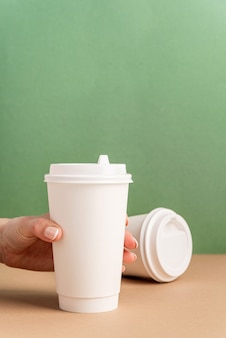 Weiße große kaffeetassen aus papier zum mitnehmen verspotten den grünen und braunen hintergrund